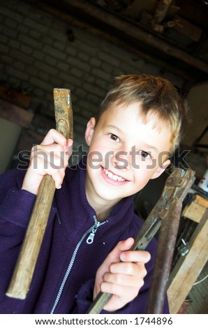 Young boy playing in garage with tools - stock photo