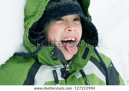 Young Boy Playing in Snow Trying to Catch Snowflakes on his Tongue - stock photo