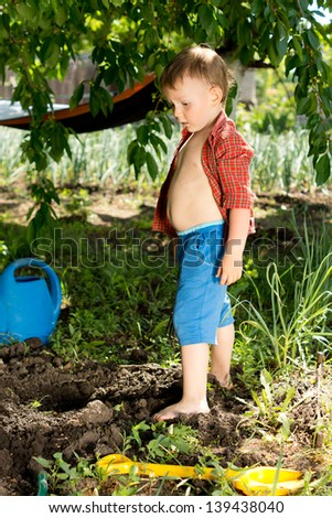Young boy playing in the garden standing in front of a newly dug hole surrounded by a plastic spade and watering can
