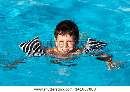 Young boy playing in the pool - stock photo