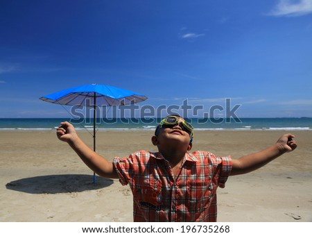 Young Boy playing on the beach with beautiful blue sky and white cloud,kid with blue sky and umbrella - stock photo