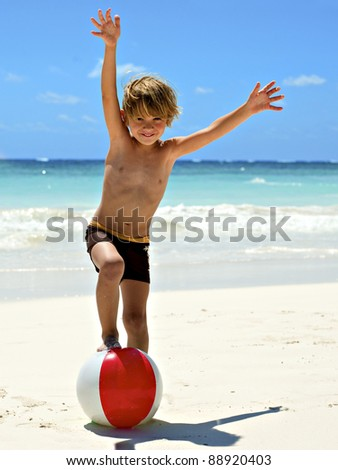 young boy playing on the tropical beach with a ball