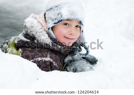 young boy playing outdoors on a snowy winter day - stock photo