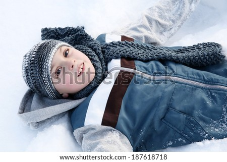 Young boy playing outside in the snow on a cold day - stock photo