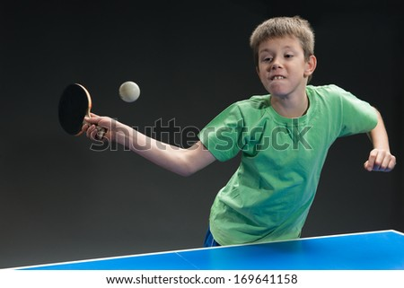 young boy playing table tennis - stock photo