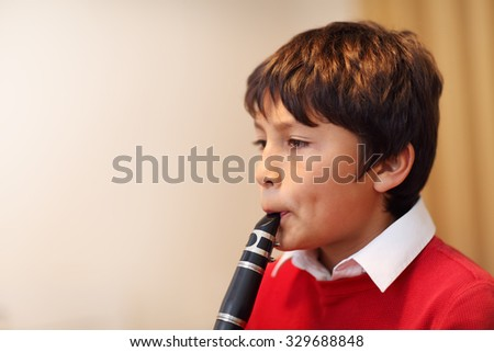 Young boy playing the clarinet - shallow depth of field - warm tones. Copy space left. - stock photo