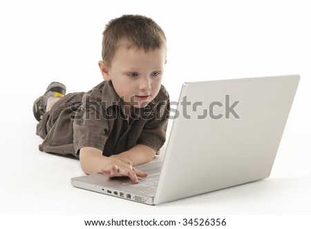 Young boy playing using a lap top on a white background