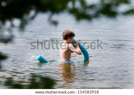 young boy playing with a floating noodle in a haliburton lake - stock photo