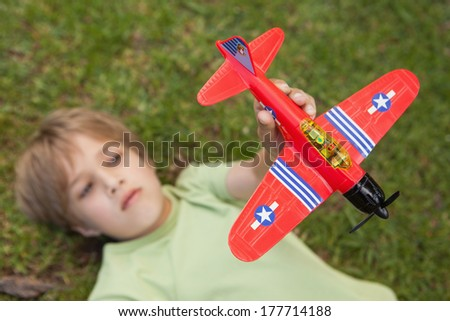 Young boy playing with a toy plane at the park - stock photo