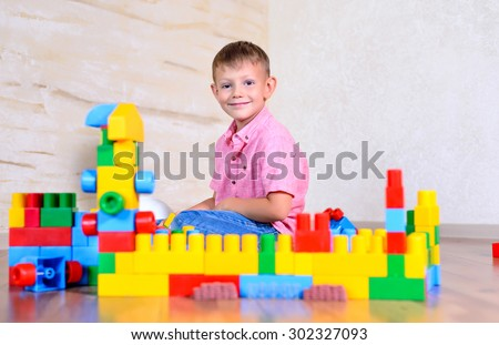 Young boy playing with colorful building blocks creating a robot and train engine turning to smile at the camera