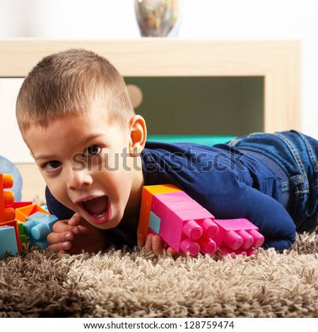 Young boy playing with cubes on the carpet - stock photo