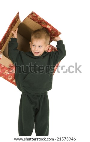Young boy playing with empty Christmas box. Isolated on white.