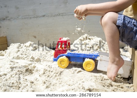 Young Boy Playing with his Plastic Truck Toy on White Sand at the Beach Under the Heat of the Sun During Summer. - stock photo