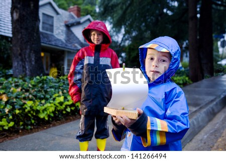 Young boy playing with toy boat in the rain wearing rain slickers and galoshes. - stock photo