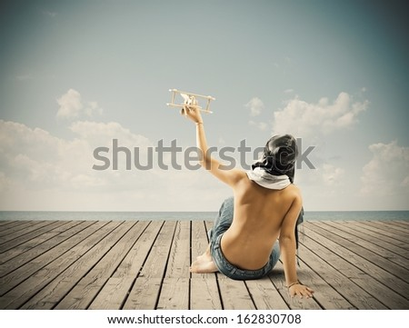 Young boy playing with toy wooden airplane - stock photo