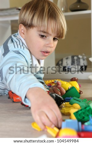 Young boy playing with toys - stock photo
