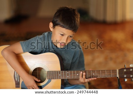 Young boy plays a guitar with very shallow depth of field and warm lighting