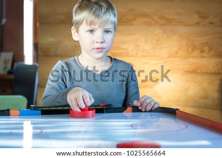 Young boy plays air hockey game at home.