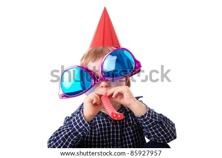 Young boy plays with huge pink and blue sunglasses, red paper hat and whistle, birthday party concept, isolated on white - stock photo
