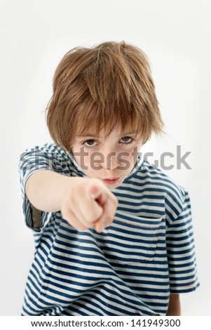 Young boy pointing and looking at camera