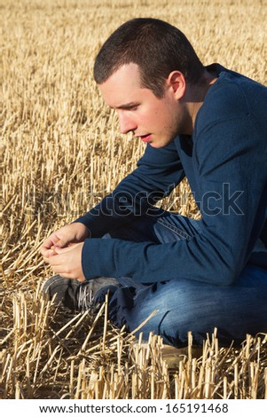 Young boy pondering profile sitting on a mown cereal field in summer - stock photo