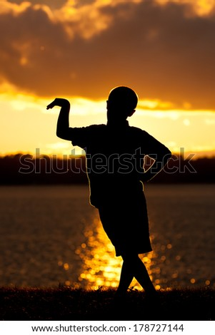 Young Boy Poses Silhouette Lake Background - stock photo