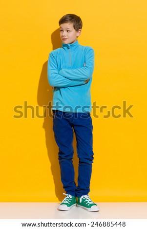 Young boy posing with arms crossed. Full length length studio shot on yellow background. - stock photo