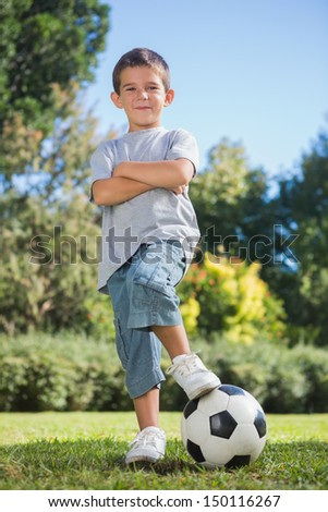 Young boy posing with football with arms crossed smiling at camera in park