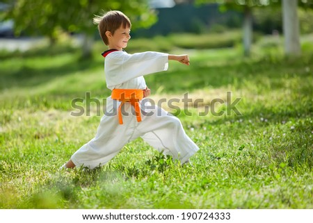 Young boy practicing martial arts outside in spring