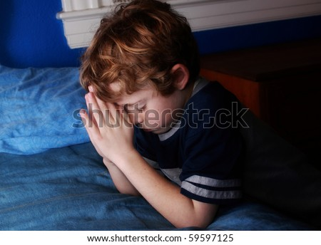 young boy praying at bedtime - stock photo