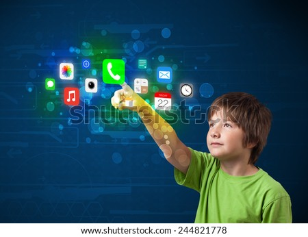 Young boy pressing colorful mobile app icons with bokeh background  - stock photo