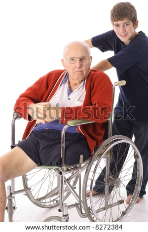 young boy pushing great grandfather in wheelchair - stock photo
