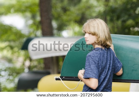 Young boy putting a canoe away for the evening - stock photo