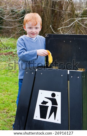 young boy putting waste food scraps into a bin - stock photo