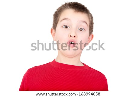 Young boy reacting with a look of amazement and awe as he stares wide eyed at the camera with his mouth forming on oh, isolated on white