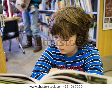 Young boy reading a book in a public library - stock photo