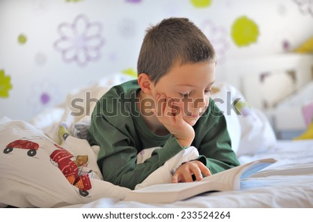 Young Boy Reading a Book in Bed in morning time - stock photo