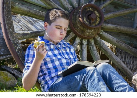 Young boy reading a book in the woods eating an apple