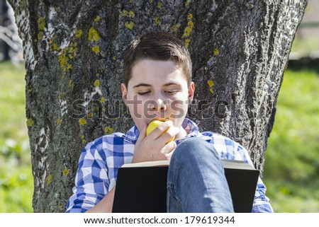 Young boy reading a book in the woods with shallow depth of field and copy space