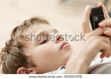 Young boy reading a text message on his mobile as he lies on his back, close up view with focus to his head - stock photo