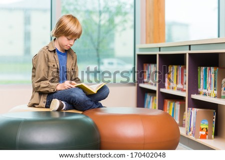 Young boy reading book in school library - stock photo