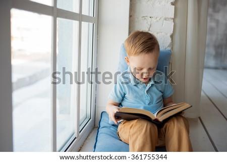 Young boy reading  book near window - stock photo