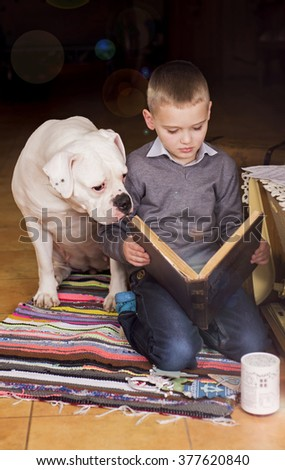 Young Boy Reading Book to His Dog. American Bulldog - stock photo