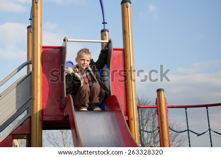 Young boy ready at the top of a slide - stock photo