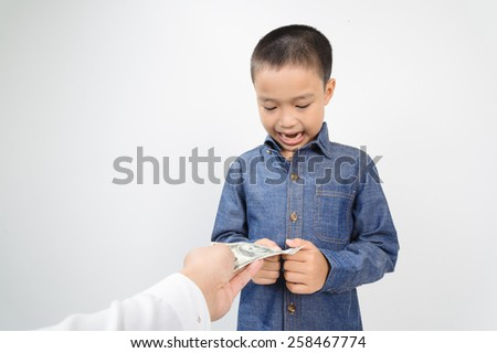 Young boy receive american bank note from hand of man - stock photo