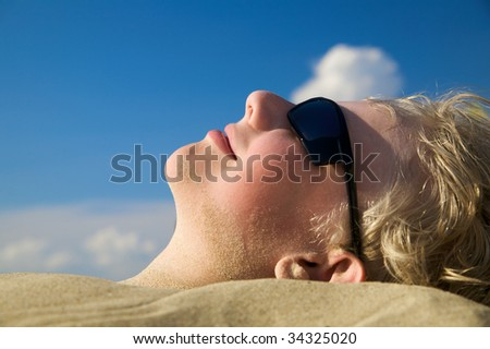 Young boy relaxing on summer beach in sunglasses - stock photo