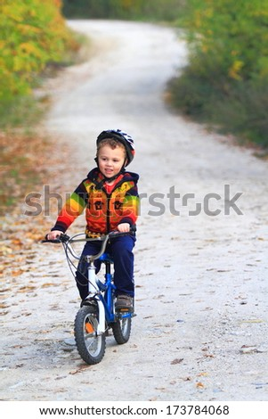 Young boy rides a bike on winding forest road - stock photo