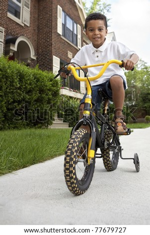 Young boy riding his first bicycle with training wheels (vertical) - stock photo