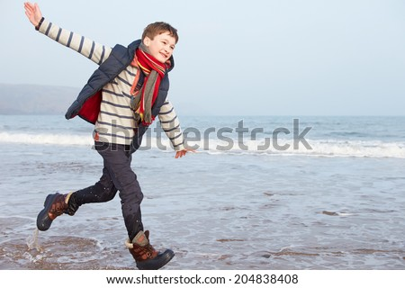 Young Boy Running Along Winter Beach - stock photo