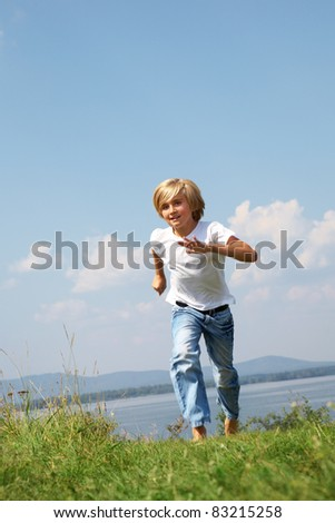 Young boy running on grass background blue sky